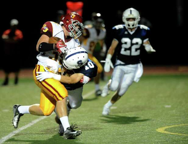 St. Joseph's Mark Hirschbeck is tackled by Staples' Jake Melnick during Friday's game at Staples High School in Westport on September 14, 2012. Photo: Lindsay Niegelberg / Stamford Advocate
