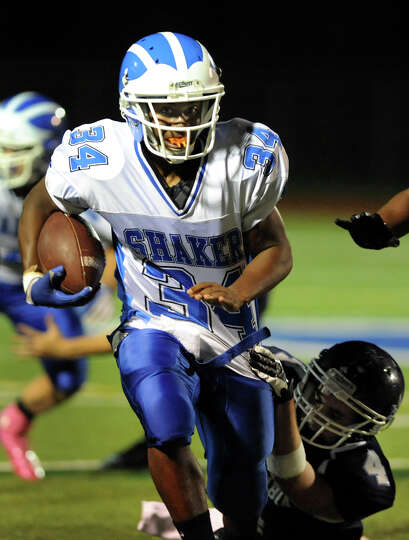 Shaker's Kenny Jackson (34), center, shakes off a tackle from Columbia's Anthony Maney (4) during th