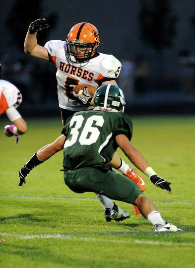 Schuylerville's Austin Cook (5) is defended by Schalmont's Nick Gallo (36)  during their football ga