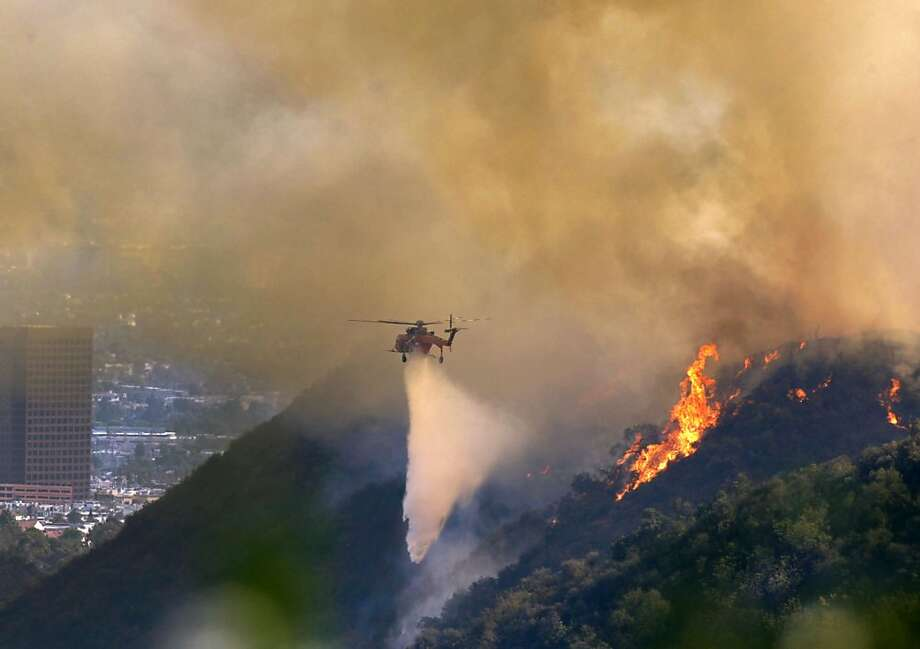 Helicopters crews make drops  on a fast-moving fire along the 405 Freeway in the Sepulveda Pass in Los Angeles that has dozens of homes in its path, Friday, Sept. 14, 2012. The blaze is expected to further slow traffic. Photo: Allen J. Schaben, Associated Press