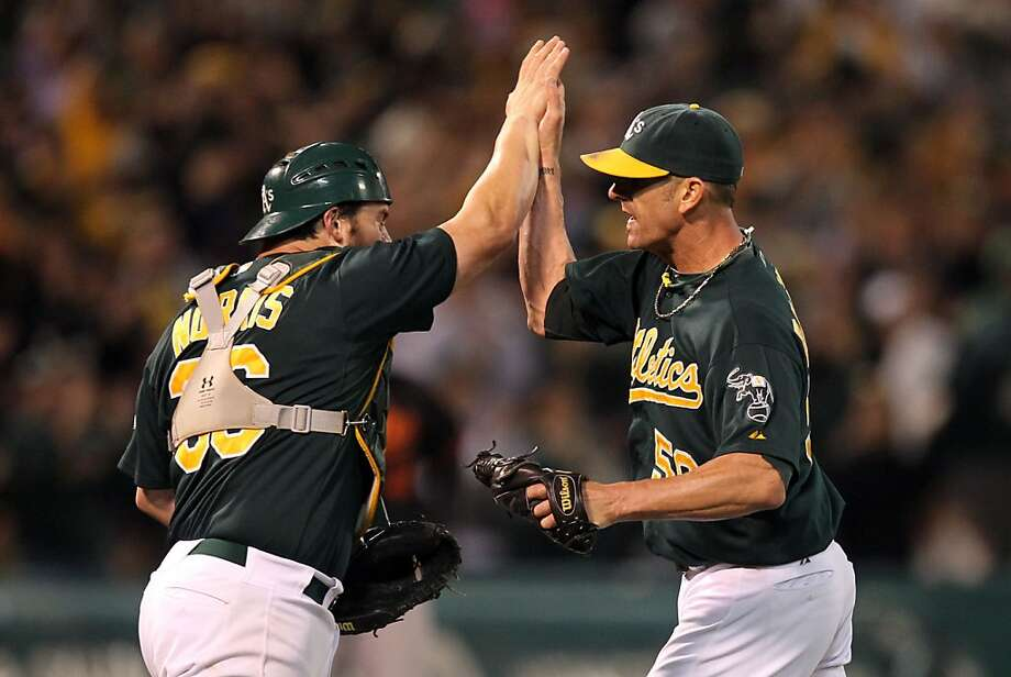 Oakland Athletics catcher Derek Norris celebrates the A's 3-2 win over the Baltimore Orioles with relief pitcher Grant Belfour Friday September 14, 2012 in Oakland California. A's won 3-2 Photo: Lance Iversen, The Chronicle