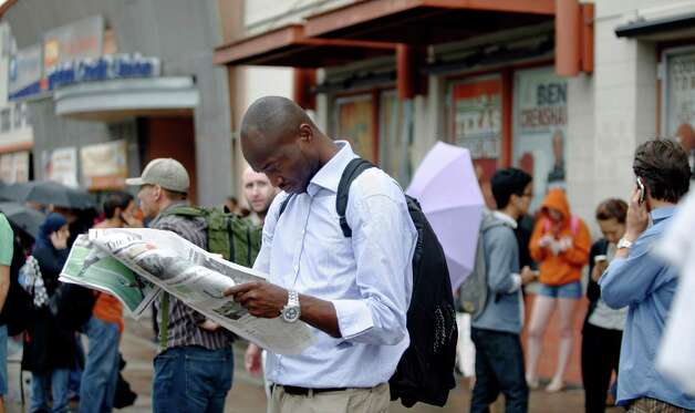 Marcel Ojinnaka, a mechanical engineering graduate student, reads a newspaper as he and other students, staff and faculty wait after being told to evacuate the campus due to a possible bomb threat at the University of Texas in Austin, Texas, Friday, Sept. 14, 2012. Photo: Thao Nguyen, Associated Press / FR159307 AP