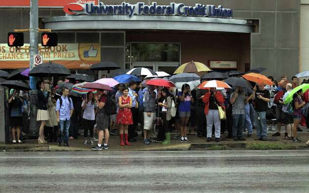 University of Texas students stand outside after evacuating buildings at The University of Texas on Friday, Sept. 14, 2012 in Austin, Texas. Thousands of people streamed off university campuses in Texas and North Dakota on Friday after phoned-in bomb threats prompted evacuations and officials warned students and faculty to get away as quickly as possible. No bombs were found on either campus by early afternoon and it was not clear whether the threats were related. Photo: AP Photo/Statesman.com,  Ricardo B.Brazziell / AUSTIN AMERICAN-STATESMAN