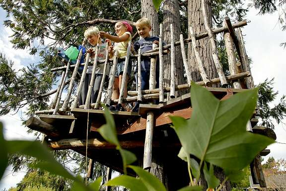 Brothers who live in the neighborhood,  Beckett , 8, (left) and Charlie, 7, (right)  Votel,  on Wednesday September 5, 2012, enjoying the treehouse, with Gene Pfeiffer's granddaughter, Parker Craver, 8, (center) her grandfather built in the backyard of his Oakland, Calif.  home.