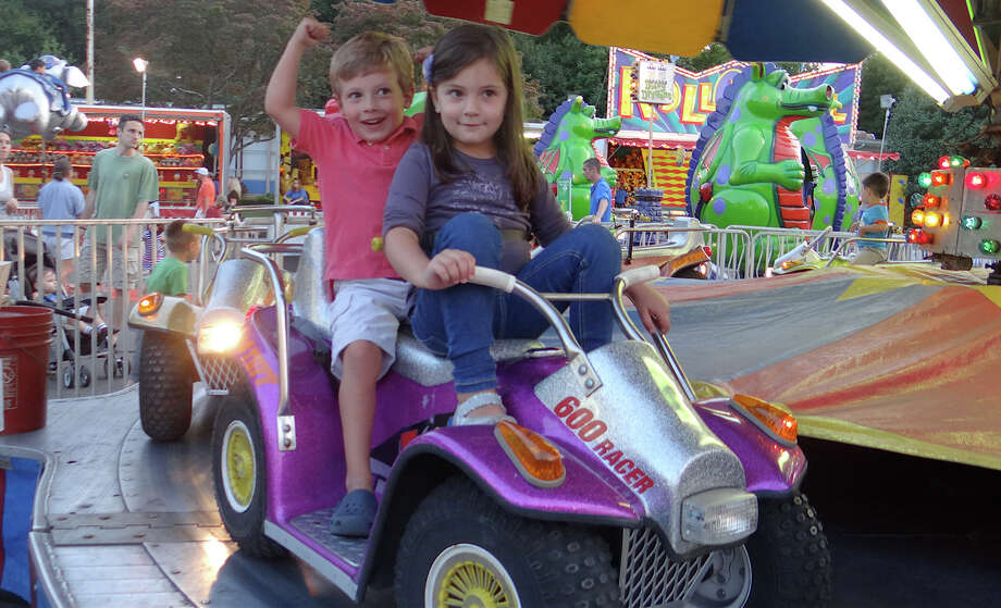 Joaquin Payo, 5, and Isabella Belistri, 4, of Fairfield, ride the Quads on Friday evening at SeptemberFest at Assumption Church. Photo: Mike Lauterborn