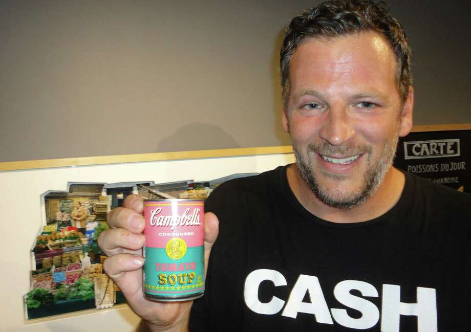 """Foodies"" exhibit juror Bill Taibe, chef and owner of Le Farm and The Whelk restaurants, shows the Andy Warhol-inspired Campbell's soup can that he got Friday as a token for helping to select the food-inspired art in Westport Arts Center exhibit. Photo: Meg Barone / Westport News freelance"