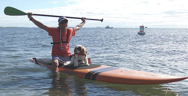 Pace Collister and his dog Arthur on their paddleboard, ready to take part in Connecticut Challenge's Stand-up Paddle Race at Penfield Beach on Saturday. Photo: Mike Lauterborn / Fairfield Citizen contributed