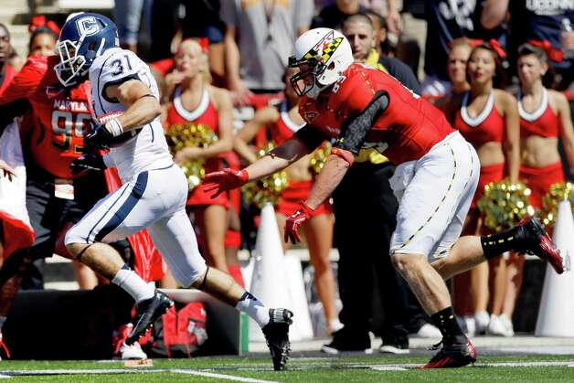 Connecticut wide receiver Nick Williams, left, outruns Maryland's Matt Furstenburg for a touchdown on a punt return in the first half of an NCAA college football game in College Park, Md., Saturday, Sept. 15, 2012. (AP Photo/Patrick Semansky) Photo: Patrick Semansky, Associated Press / AP