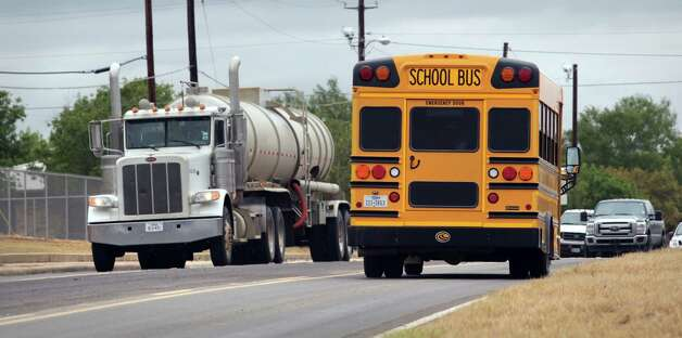 Cotulla school buses have to deal with increased traffic from the oil industry in the area.  District officials have had to find creative ways to help employees afford area housing since the oil industry has driven housing cost high.  Friday, Sept. 14, 2012. Photo: Bob Owen, San Antonio Express-News / © 2012 San Antonio Express-News