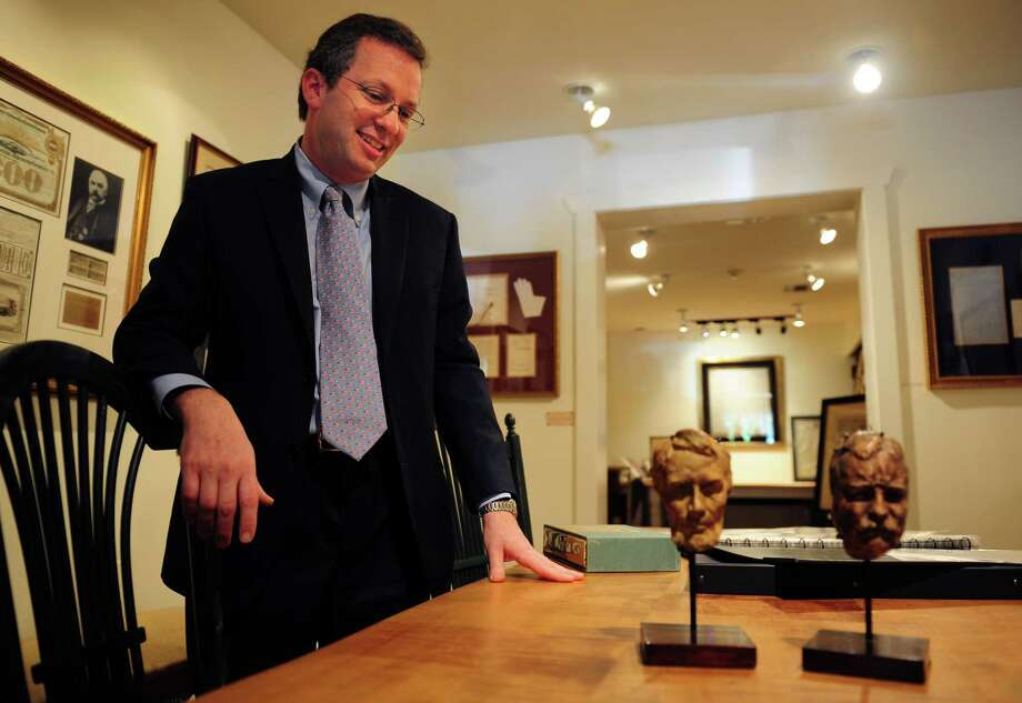 Seth Kaller looks down at Gutzon Borglums' busts of Abraham Lincoln and Theodore Roosevelt at Rockwell Art and Framing.  One of seven galleries in Connecticut owned by Stephen Rockwell Desloge, a former executive with Enterprise Rent A Car, the Westport gallery, Rockwell Art and Framing, recently started specializing in historic documents and other memorabilia. Photo: Autumn Driscoll / Connecticut Post