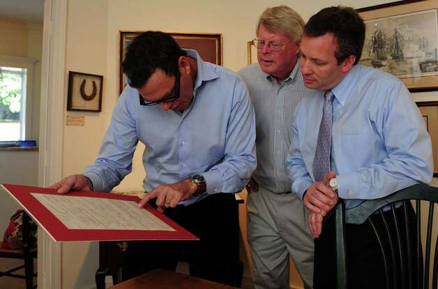 John Reznikoff, Stephen Rockwell Desloge and Seth Kaller look over a document at  Rockwell Art and Framing.  One of seven galleries in Connecticut owned by Stephen Rockwell Desloge, a former executive with Enterprise Rent A Car, the Westport gallery, Rockwell Art and Framing, recently started specializing in historic documents and other memorabilia. Photo: Autumn Driscoll / Connecticut Post