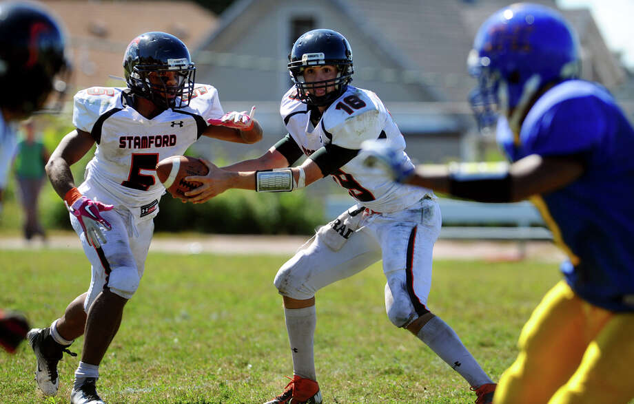 Stamford QB Tyler Kane hands the ball off to #5 Cameron Webb, during boys football action against Harding in Bridgeport, Conn. on Saturday September 15, 2012. Photo: Christian Abraham / Connecticut Post