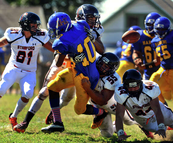 Harding QB Jahaad Williams looses the football as he is tackled by Stamford's #55 Rodrigo Denapoliand #52 Miguel Nieto, during boys football action in Bridgeport, Conn. on Saturday September 15, 2012. Stamford recovered the ball. Photo: Christian Abraham / Connecticut Post