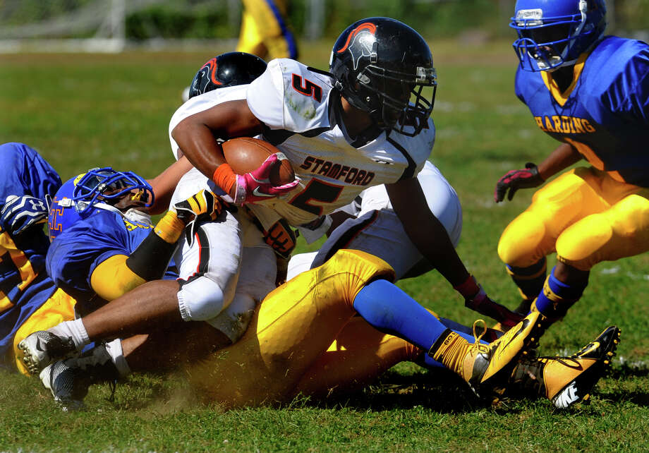 Stamford's #5 Cameron Webb gets tackled by Harding's #5 Reggie David, during boys football action in Bridgeport, Conn. on Saturday September 15, 2012. Photo: Christian Abraham / Connecticut Post