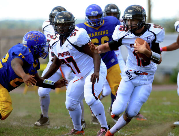 Harding's #22 Tashuan Ballard, left, rushes towards Stamford QB Tyler Kane, during boys football action in Bridgeport, Conn. on Saturday September 15, 2012. Ballard was able to reach Kane for the tackle. Photo: Christian Abraham / Connecticut Post