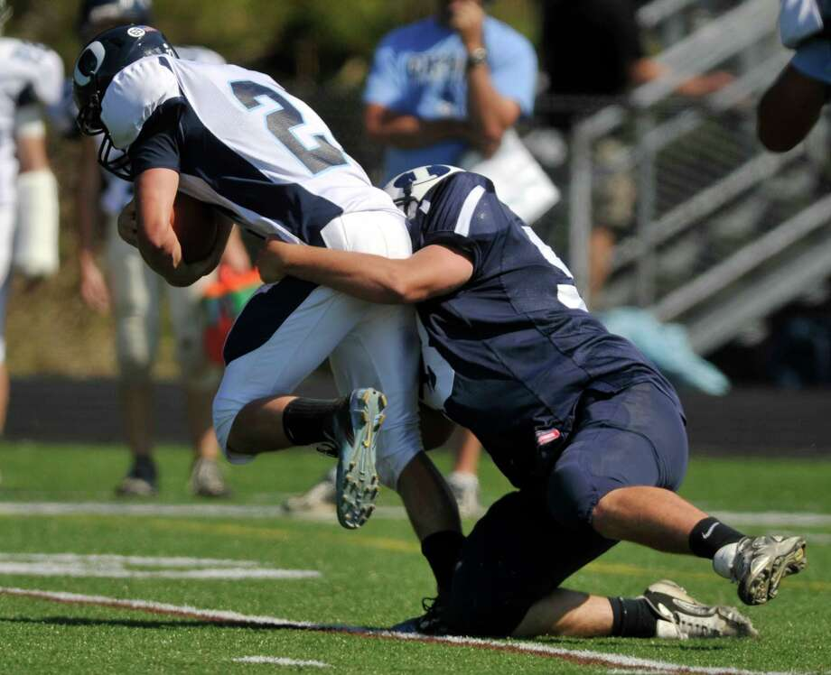 Oxford's Steve Persson is brought down by Immaculate's Riley Cross during their game at Immaculate High School in Danbury on Saturday, Sept. 15, 2012. Oxford won, 35-0. Photo: Jason Rearick / The News-Times