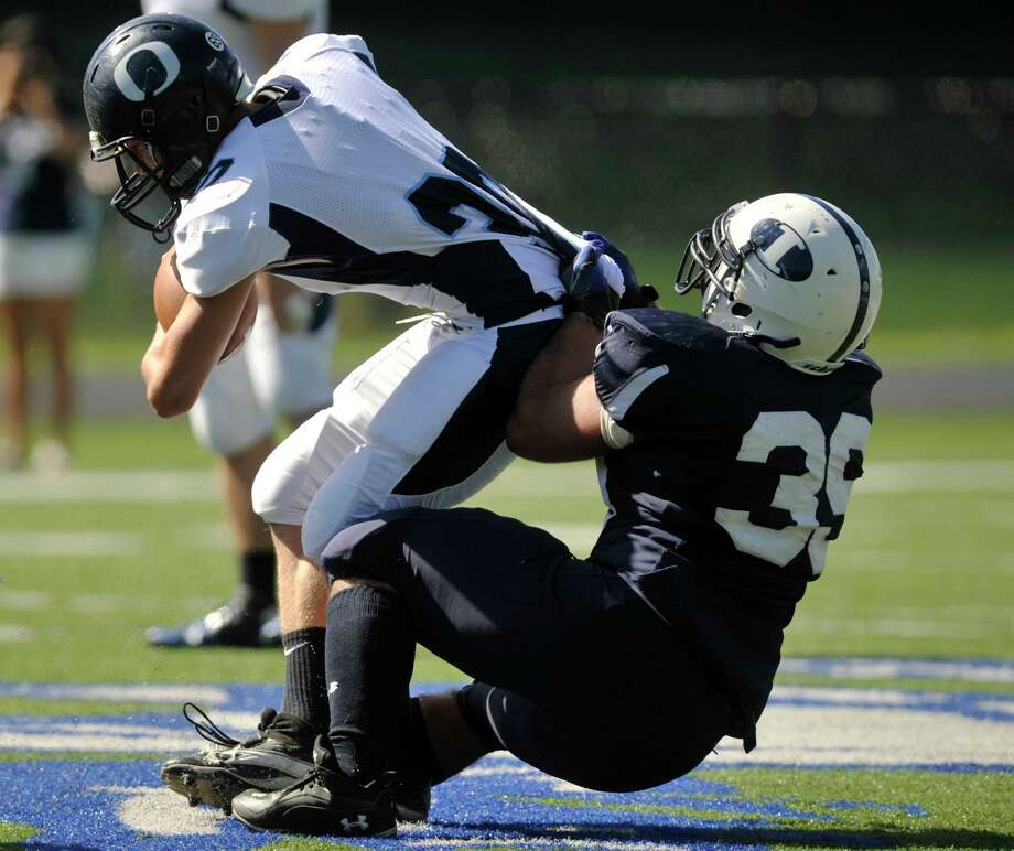 Oxford's Dan Trombetta is brought down by Immaculate's Steven Ghossaini during their game at Immaculate High School in Danbury on Saturday, Sept. 15, 2012. Oxford won, 35-0. Photo: Jason Rearick / The News-Times