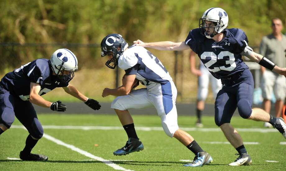 Oxford's Steve Persson runs the ball while under pressure from Shane Murphy, left, and Michael Woods during their game at Immaculate High School in Danbury on Saturday, Sept. 15, 2012. Oxford won, 35-0. Photo: Jason Rearick / The News-Times