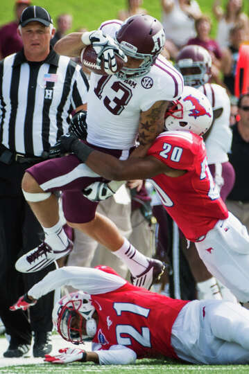 Texas A&M wide receiver Mike Evans is pushed out of bounds by SMU defensive backs Ryan Smith and Ken