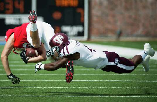 SMU wide receiver Cole Loftin is upended by Texas A&M defensive back Toney Hurd Jr. during the second quarter. Photo: Smiley N. Pool, Houston Chronicle / © 2012  Houston Chronicle