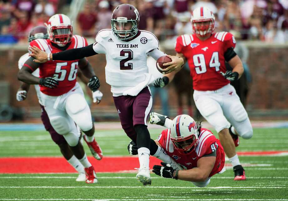 Texas A&M quarterback Johnny Manziel breaks free from SMU defensive tackle Aaron Davis on a 48-yard touchdown run. Photo: Smiley N. Pool, Houston Chronicle / © 2012  Houston Chronicle