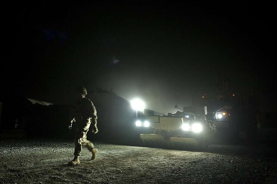 An Infantry man from the 1st platoon, Delta coy., US army walks infront of a tactical mine-resistant vehicle through a section that requires a ground-guide at Lindsey foward operating base on September 15, 2012 in Kandahar province, Afghanistan. Two NATO soldiers were shot dead today by a man believed to be a member of a controversial Afghan police force in southern Afghanistan, the US-led military said. The attack means that so far this year, Afghan security personnel have shot dead at least 47 NATO soldiers, the majority of them American, threatening to jeopardise Western plans to train Afghan forces to take over when they leave in 2014.  AFP PHOTO/Tony KARUMBATONY KARUMBA/AFP/GettyImages Photo: Tony Karumba, AFP/Getty Images
