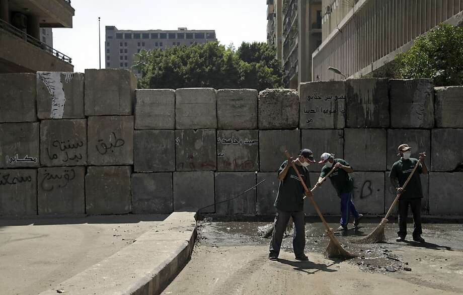 An Egyptian crew cleans up the area where protests were held near the U.S. Embassy in Cairo. Photo: Khalil Hamra, Associated Press