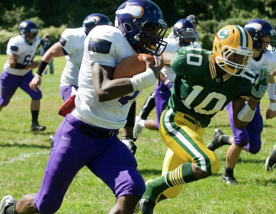 Westhill's Davell Cotterell carries as Trinity's Chris Durant closes in as Trinity Catholic High School hosts Westhill in a football game Saturday, Sept. 15, 2012. Trinity won the game, 28-10. Photo: Keelin Daly / Stamford Advocate Freelance