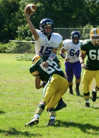 Trinity's Joseph Carrizzo applies pressure to Westhill quarterback Ryan Coppolla as Trinity Catholic High School hosts Westhill in a football game Saturday, Sept. 15, 2012. Trinity won the game, 28-10. Photo: Keelin Daly / Stamford Advocate Freelance