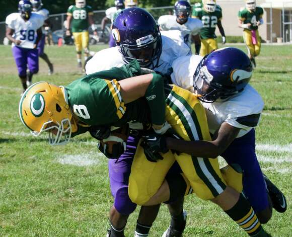Westhill's Jordan Fields and Branden Turner tackle Trinity's Connor Amann as Trinity Catholic High School hosts Westhill in a football game Saturday, Sept. 15, 2012. Trinity won the game, 28-10. Photo: Keelin Daly / Stamford Advocate Freelance