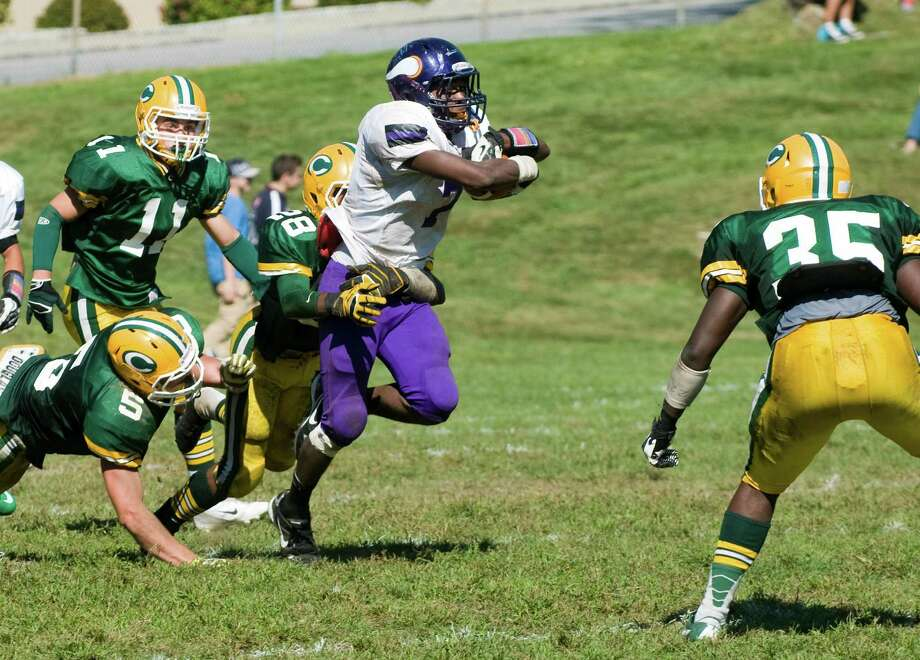 Westhill's Davell Cotterell pushes on as Trinity's Randy Polonia tackles as Trinity Catholic High School hosts Westhill in a football game Saturday, Sept. 15, 2012. Trinity won the game, 28-10. Photo: Keelin Daly / Stamford Advocate Freelance