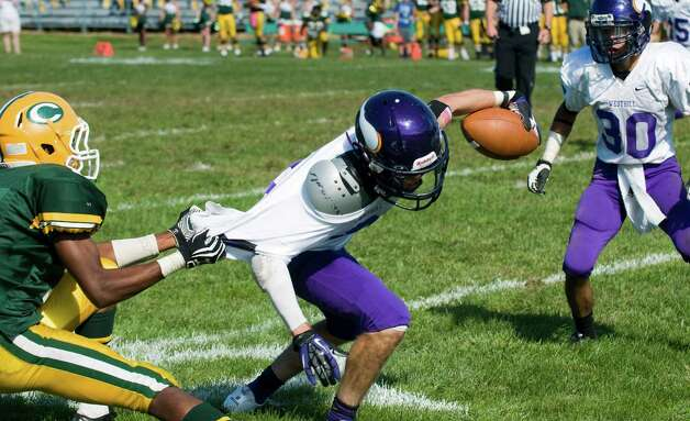 Trinity's Neno Merritt puts as stop to Westhill's Dante Farnolgi as Kyle Cruz looks on as Trinity Catholic High School hosts Westhill in a football game Saturday, Sept. 15, 2012. Trinity won the game, 28-10. Photo: Keelin Daly / Stamford Advocate Freelance