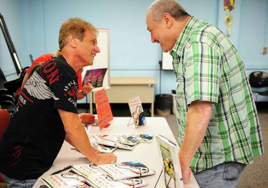 """Singer, song writer Gary DeCarlo talks with Tom Bottillo, of Bridgeport, during a discussion and book signing for """"Na Na Hey Hey Kiss Him Goodbye,"""" Saturday, Sept. 15, 2012 at the Bridgeport Public Library, Burroughs and Saden branch.  DeCarlo wrote the book with co-author author Mary Rose Scinto which is about the story behind the song and his role as lead vocalist. Photo: Autumn Driscoll / Connecticut Post"""