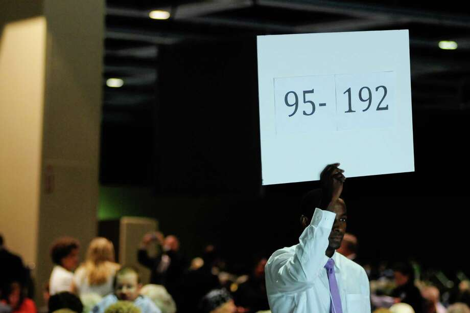 A volunteer holds up a sign as people stream in the hall doors before a campaign fundraiser for Democratic gubernatorial candidate Jay Inslee at the Washington State Convention Center on Saturday, September 15, 2012. The event, which featured former President Bill Clinton, was described by speakers as one of the largest political gatherings Seattle has seen, brought in roughly $750,000 and about 3,000 people. Photo: LINDSEY WASSON / SEATTLEPI.COM