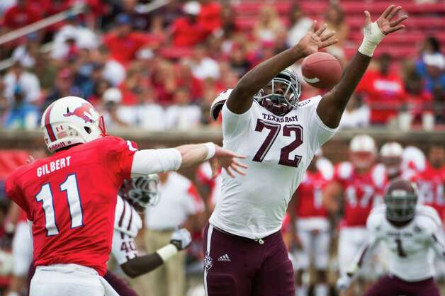 Texas A&M defensive lineman Gavin Stansbury (72) applies pressure to Southern Methodist quarterback Garrett Gilbert (11) during the second half of an NCAA football game at Ford Stadium, Saturday, Sept. 15, 2012, in Dallas. Texas A&M won the game 48-3. Photo: Smiley N. Pool, Houston Chronicle / © 2012  Houston Chronicle