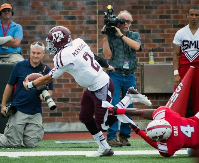 Texas A&M quarterback Johnny Manziel (2) gets past Southern Methodist defensive back Jeremy Gray (4)