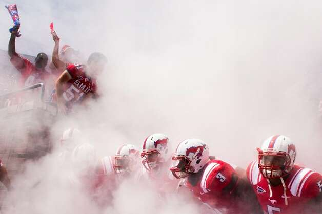 Southern Methodist players prepare to take the field through a cloud of smoke before an NCAA football game against Texas A&M at Ford Stadium, Saturday, Sept. 15, 2012, in Dallas. ( Smiley N. Pool / Houston Chronicle ) (Houston Chronicle)