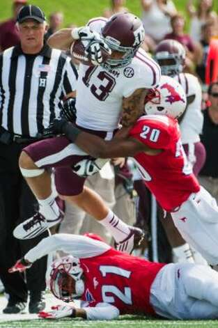 Texas A&M wide receiver Mike Evans (13) is pushed out of bounds by Southern Methodist defensive backs Ryan Smith (20) and Kenneth Acker (21) during the first quarter of an NCAA football game at Ford Stadium, Saturday, Sept. 15, 2012, in Dallas. ( Smiley N. Pool / Houston Chronicle ) (Houston Chronicle)