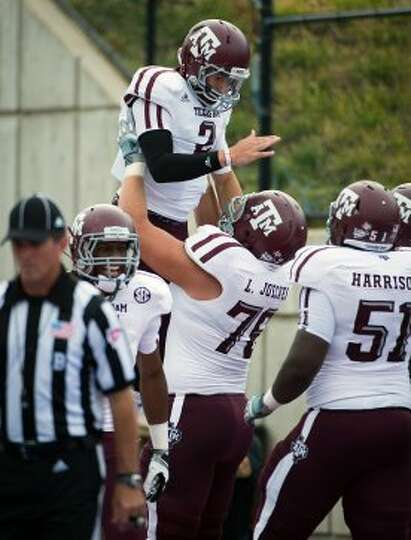 Texas A&M quarterback Johnny Manziel (2) is lifted by offensive linesman Luke Joeckel (76) in celebr
