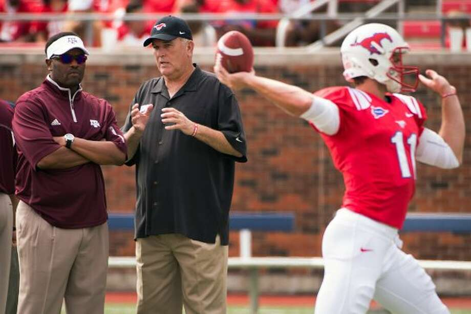 Texas A&M head coach Kevin Sumlin, left, chats with Southern Methodist head coach June Jones as the teams warm up before an NCAA football game at Ford Stadium, Saturday, Sept. 15, 2012, in Dallas. Southern Methodist quarterback Garrett Gilbert (11) tosses a pass at right. ( Smiley N. Pool / Houston Chronicle ) (Houston Chronicle)