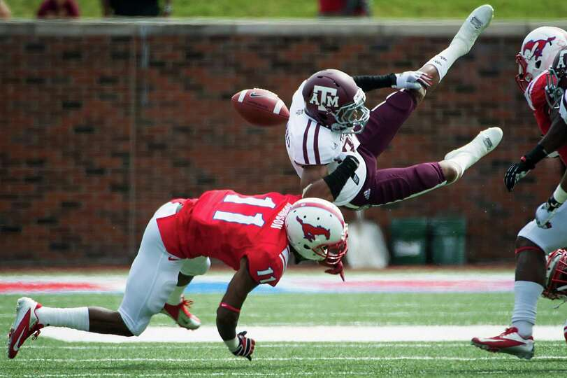 Texas A&M's Dustin Harris (22) fumbles as he is hit by Southern Methodist's Keith Robinson (11) on a