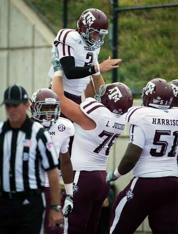 Texas A&M quarterback Johnny Manziel (2) is lifted by offensive linesman Luke Joeckel (76) in celebration of a touchdown run during the second half of an NCAA football game against Southern Methodist at Ford Stadium, Saturday, Sept. 15, 2012, in Dallas. Texas A&M won the game 48-3. Photo: Smiley N. Pool, Houston Chronicle / © 2012  Houston Chronicle
