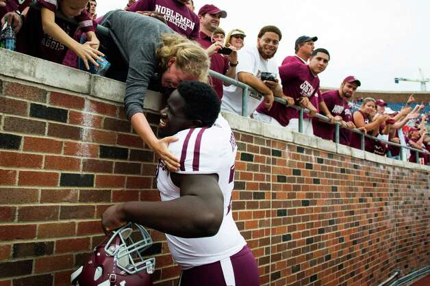 Texas A&M offensive linesman Germain Ifedi celebrates with fans following the Aggies 48-3 victory over Southern Methodist in an NCAA football game at Ford Stadium, Saturday, Sept. 15, 2012, in Dallas. Photo: Smiley N. Pool, Houston Chronicle / © 2012  Houston Chronicle