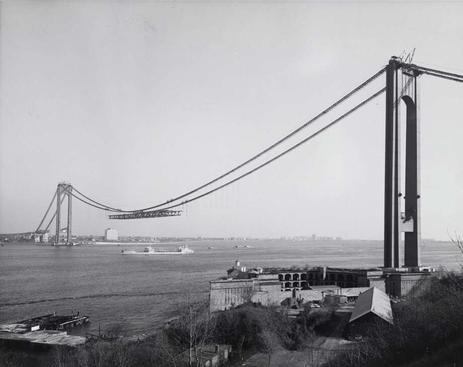 "This Dec. 4, 1963 photo provided by the Museum of the City of New York shows New York's Verrazano-Narrows Bridge, linking Brooklyn to Staten Island, under construction. Beyond the ferry, the Verrazano-Narrows Bridge and maybe the Fresh Kills landfill, few people outside Staten Island know of its rich history as a strategic site in New York Harbor, a farming center, a recreational haven and a suburban retreat.  A new exhibition aims to rectify that. ""From Farm to City: Staten Island 1661-2012"" opened at the Museum of the City of New York on Thursday and runs through Jan. 21. (AP Photo/Museum of the City of New York) Photo: Museum Of The City Of New York"