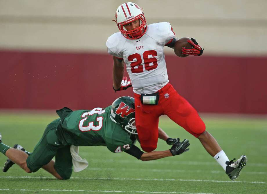 Katy's Rodney Anderson (26) escapes the tackle of The Woodlands' Tyler Murphy during the first half of a high school football game, Saturday, September 15, 2012 at Woodforest Bank Stadium in Shenandoah, TX. Photo: Eric Christian Smith, For The Chronicle