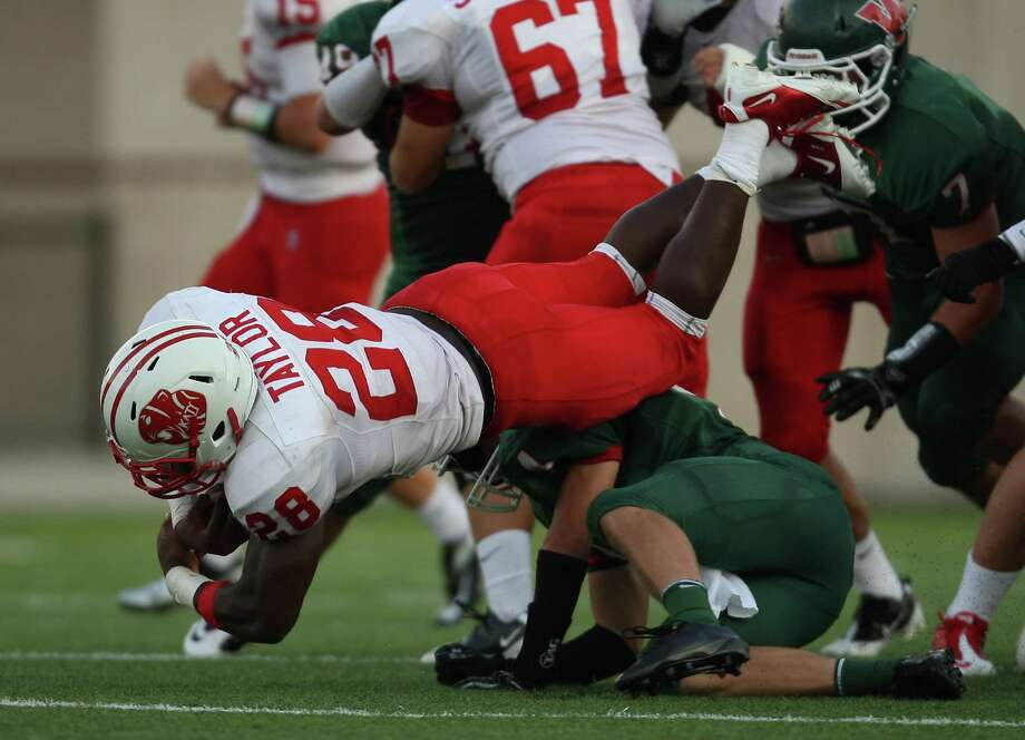 Katy's Adam Taylor (28) is upended by The Woodlands' Tyler Patrick during the first half of a high school football game, Saturday, September 15, 2012 at Woodforest Bank Stadium in Shenandoah, TX. Photo: Eric Christian Smith, For The Chronicle