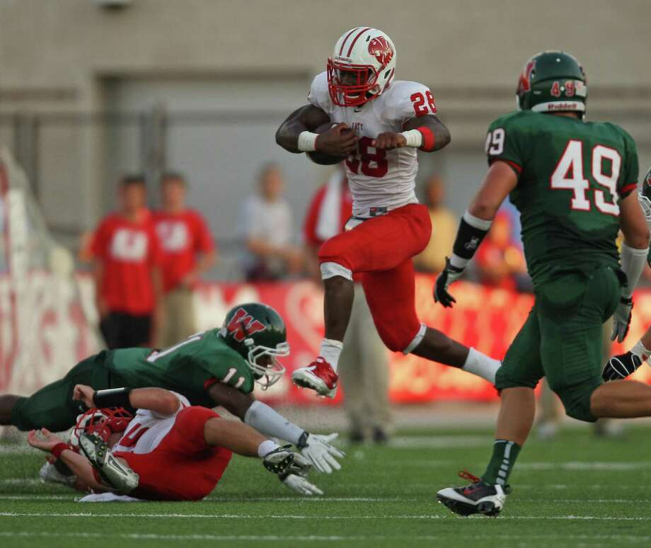 Katy's Adam Taylor (28) leaps past the tackle of The Woodlands' Kolbi Brown during the first half of a high school football game, Saturday, September 15, 2012 at Woodforest Bank Stadium in Shenandoah, TX. Photo: Eric Christian Smith, For The Chronicle