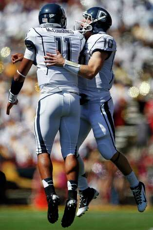 Connecticut quarterback Scott McCummings, left, celebrates with Chandler Whitmer after McCummings scored a touchdown in the first half of an NCAA college football game against Maryland in College Park, Md., Saturday, Sept. 15, 2012. Connecticut won 24-21. (AP Photo/Patrick Semansky) Photo: Patrick Semansky, Associated Press / AP