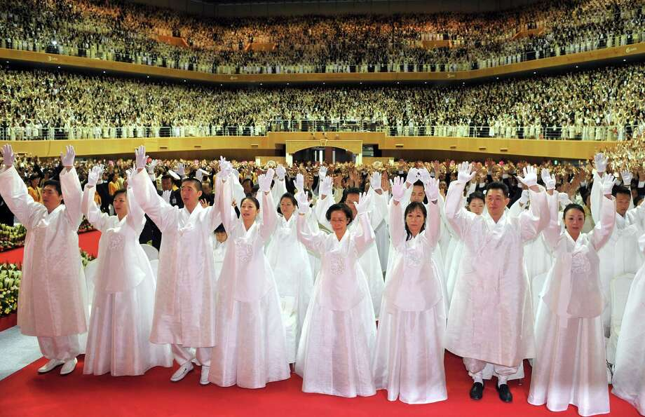 """Hyung-Jin Moon, third from left, Unification Church founder Sun Myung Moon's youngest son and successor along with followers gesture for the late Moon during his funeral ceremony at the Cheongshim Peace World Center in Gapyeong, about 60 km east of Seoul, on September 15, 2012. More than 30,000 mourners, many weeping openly, attended the elaborate, flower-strewn funeral in South Korea on September 15 of their """"messiah"""" and Unification Church founder Sun Myung Moon. Photo: JUNG YEON-JE, AFP/Getty Images / AFP"""