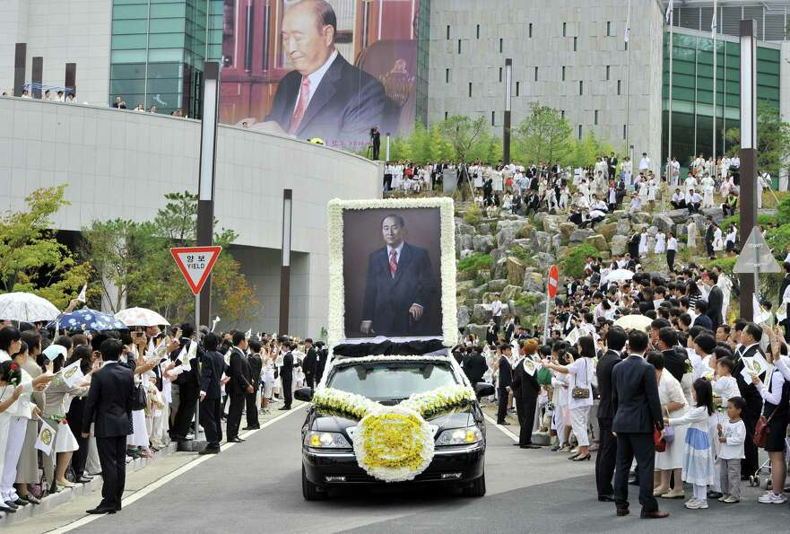 A funeral car loaded with a portrait of late Unification Church founder Sun Myung Moon drives past f